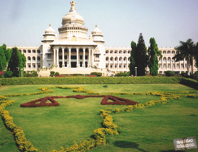 """Bangalore. It is called """"Vidhana Soudha"""". You could call it as Karnata Parliament Building.   The sign in the bottom right reads """"Do not walk on grass"""""""